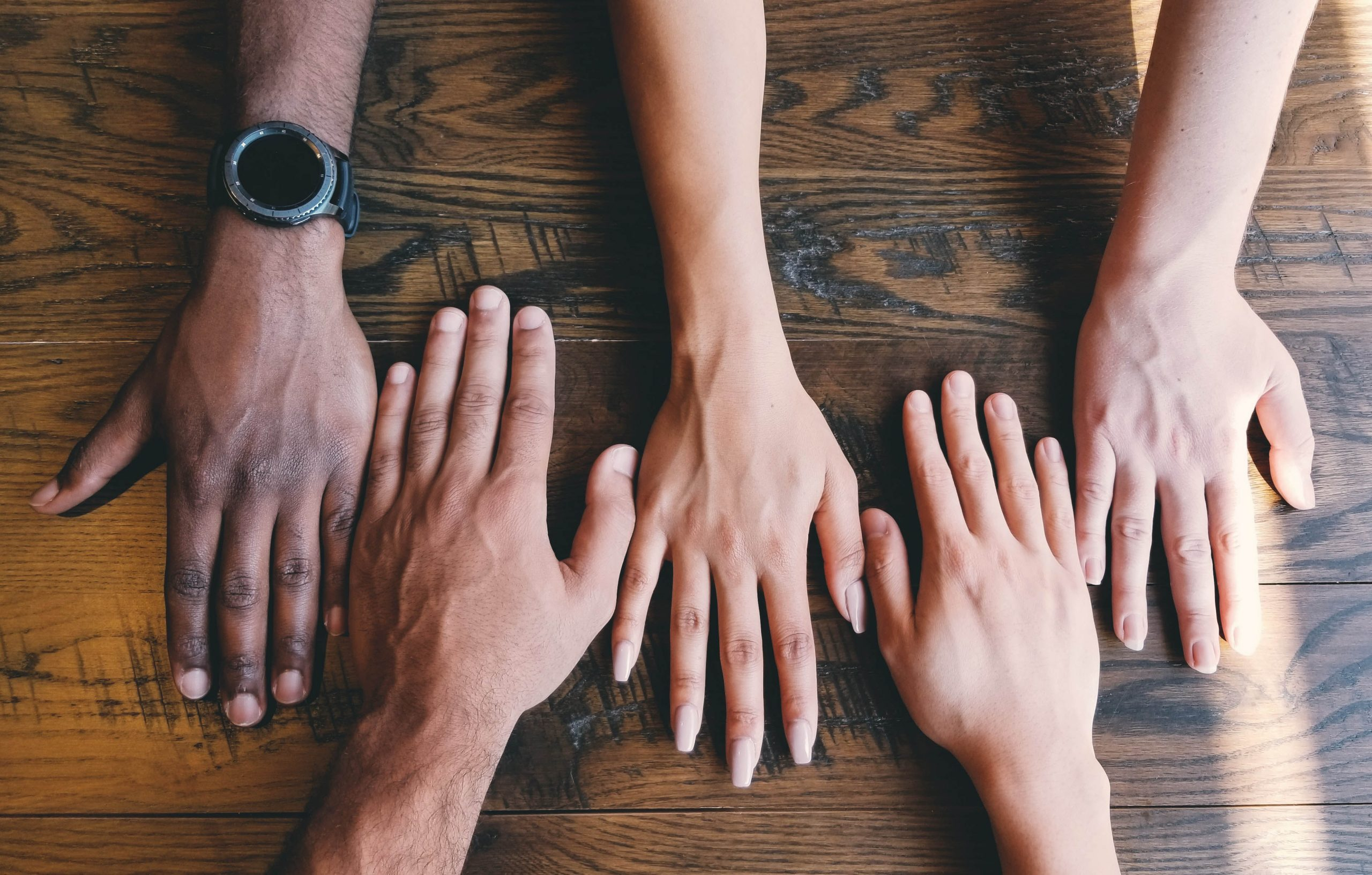 diverse hands across a table
